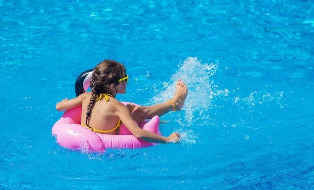 아이는 수영장에서 원을 그리며 수영합니다. 선택적 초점입니다. 아이.