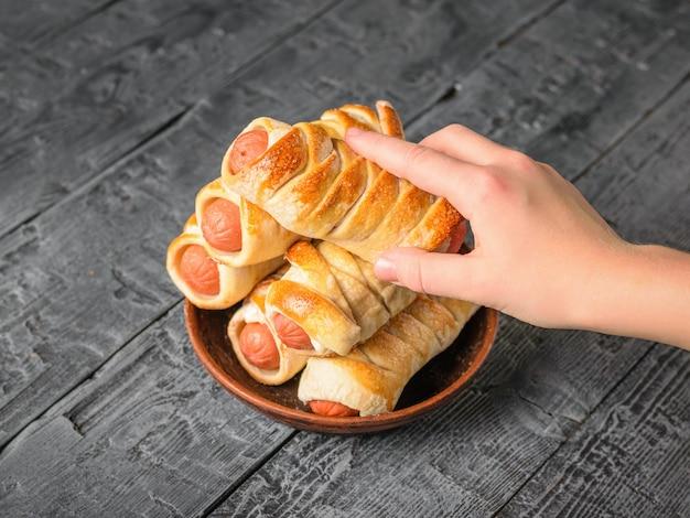 子供は粘土ボウルから彼の右手ソーセージ生地を取り出します。生地とソーセージで作った美味しいお肉スナック。