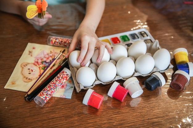 아이는 부활절 장식을 위해 테이블 위의 제작 대에서 달걀 하나를 가져옵니다.