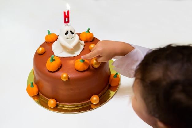 Ребенок трогает пальчиком торт, украшенный на хэллоуин тыквенными привидениями и горящим ...