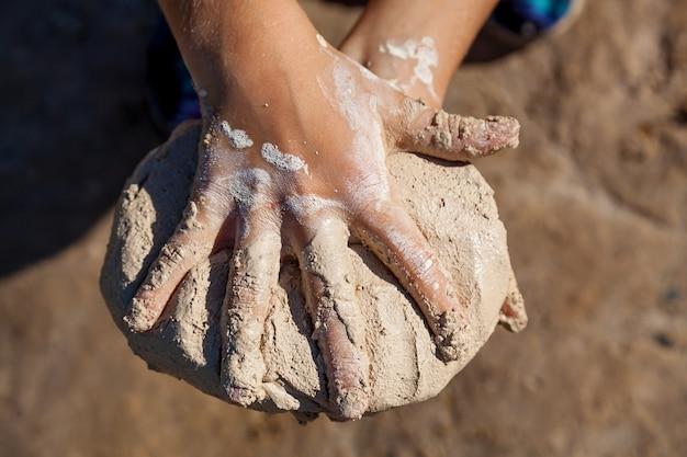 子供は濡れた砂を使って円の形でフィギュアを作ろうとします子供のクローズアップビュー