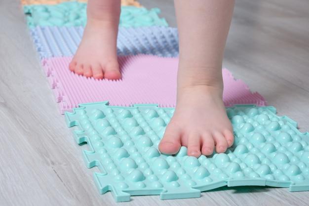 Ребенок ходит по коврику для массажа стоп в домашних условиях.