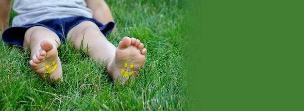Ребенок лежал на зеленой траве. улыбнись красками на ногах и руках. ребенок весело на открытом воздухе в весеннем парке. выборочный фокус. природа