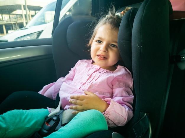 子供はチャイルドシートに座っている車の悲しい幼児の船酔いでした Premium写真
