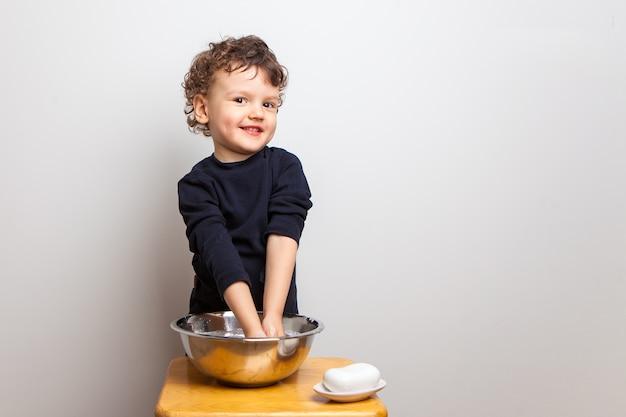아이는 조밀 한 비누 막대로 손을 씻습니다.