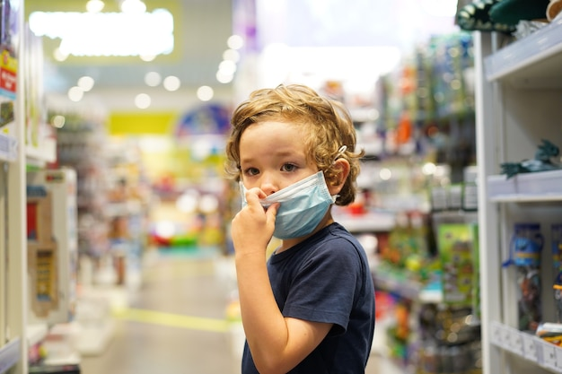 아이는 상점에서 보호 마스크를 착용합니다. covid-19 격리 중 안전, 건강 보호.