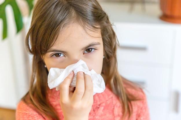 子供は鼻水をナプキンで拭きます。セレクティブフォーカス。人。