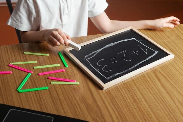 Ребенок пишет числа на доске и считает с разноцветных счетных палочек домика.