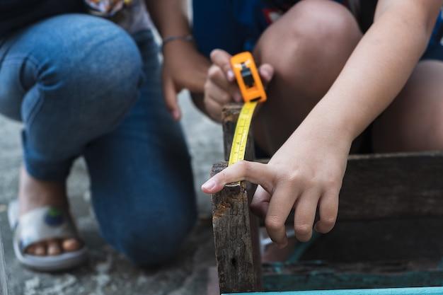Дети ремонтируют деревянное с помощью карандаша и рулетки.