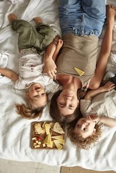 아이들은 엄마와 함께 침대에 누워 치즈를 먹습니다.
