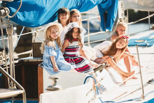 오렌지 주스를 마시는 바다 요트의 보드에 아이들. 푸른 하늘 야외에 대 한 청소년 또는 어린이 소녀. 화려한 옷. 키즈 패션, 화창한 여름, 강 및 휴일 개념.