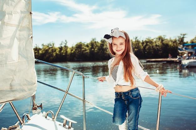 オレンジジュースを飲む海のヨットに乗っている子供たち。屋外の青い空に対して10代または子供の女の子。