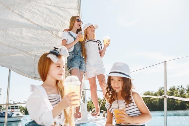 オレンジジュースを飲む海のヨットに乗っている子供たち