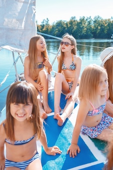 海のヨットに乗っている子供たち。屋外の青い空に対して10代または子供の女の子。カラフルな服。キッズファッション、晴れた夏、川、休日のコンセプト。