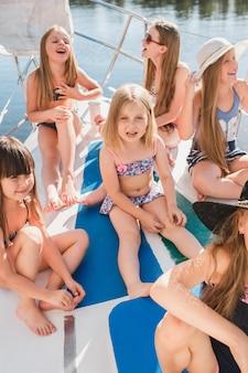 海のヨットに乗っている子供たち。 10代または子供の女の子の屋外。カラフルな服。キッズファッション、晴れた夏、川、休日のコンセプト。