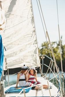 海のヨットに乗っている子供たち。 10代または子供の女の子の屋外。