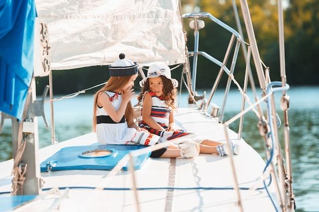 海のヨットに乗っている子供たち。
