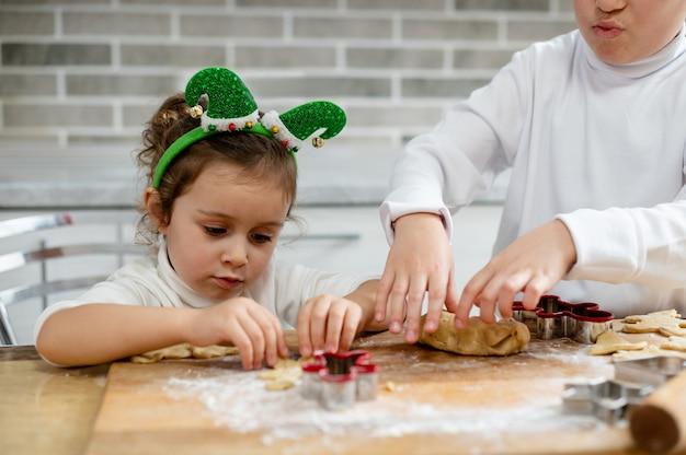 아이들은 반죽에서 크리스마스 진저 브레드를 준비합니다.