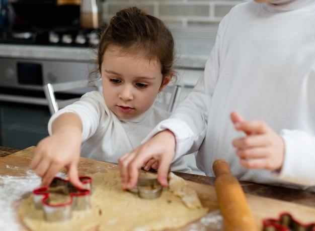Дети вырежут из рождественского печенья специальные формы.