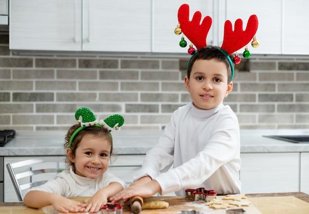 머리에 크리스마스 장식을 한 아이들은 반죽에서 크리스마스 진저 브레드를 준비합니다.