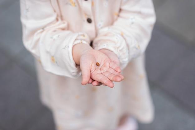 子供の手はてんとう虫環境保護の概念を保持しています