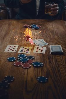 木製のテーブルでギャンブル、飲み物、トランプのチップ。ポーカーのコンセプト