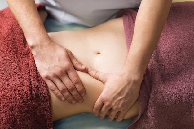 척추 지압사는 복부에 마사지를 수행합니다.