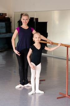 Хореограф обучает ребенка балетным позициям