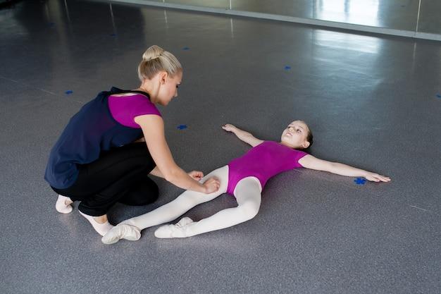 Хореограф учит ребенка правильной осанке.