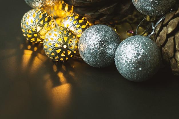 黒背景にクリスマスボールと松のコーン。