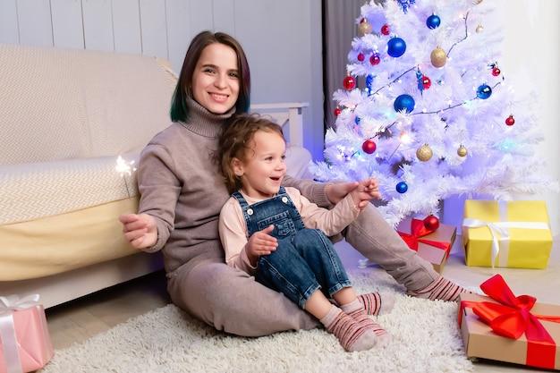 크리스마스, 엄마와 딸이 폭죽을 밝혔습니다.