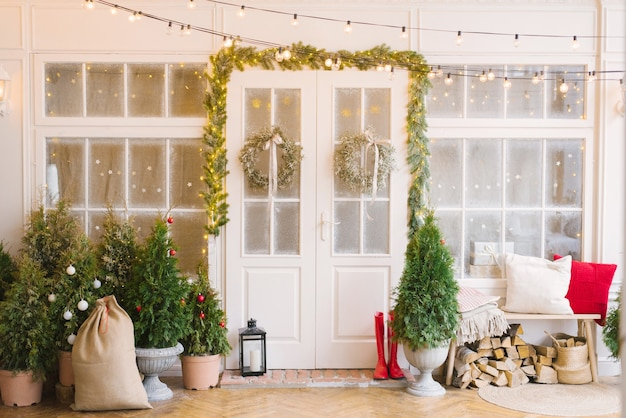クリスマスポーチは小さなクリスマスツリーとランタンで飾られています