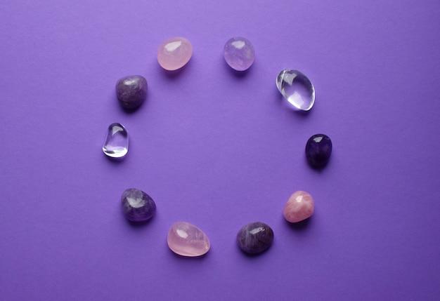 円には天然ミネラルが並んでいます。異なる色の半貴石を加工しました。アメジストとローズクォーツ。紫色の背景に宝石のフレーム。