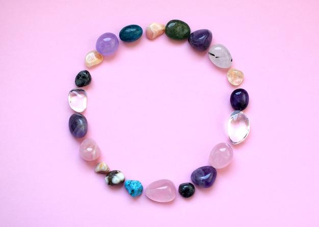 원에는 천연 미네랄이 늘어서 있습니다. 다양한 색상의 준보석, 가공되지 않은 원석. 자수정, 장미 석영, 마노, 인회석, 분홍색 배경의 어벤츄린