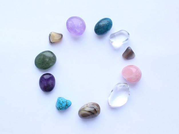 Круг выложен натуральными минералами. полудрагоценные камни разного цвета, необработанные и обработанные. аметист, розовый кварц, агат, апатит, авантюрин на белой стене.