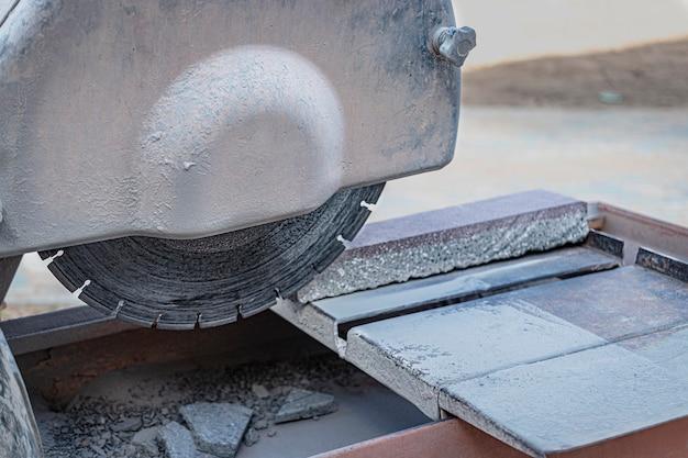 원형 다이아몬드 톱은 화강암 보도 타일을 자릅니다. 콘크리트 절단기 클로즈업입니다.