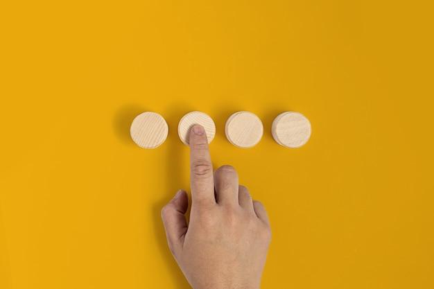 노란색 배경에 원형 나무 블록을 놓고 버튼을 누르는 것처럼 손 제스처가 나무 블록을 누릅니다. 텍스트, 포스터, 모형 템플릿을 위한 복사 공간이 있는 배너.