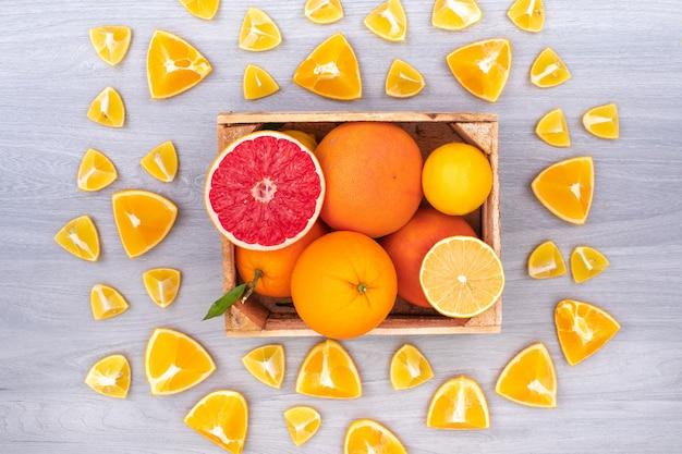 オレンジに囲まれた木製の箱に柑橘系の果物