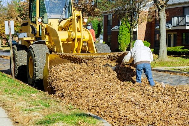 葉の掃除に関する都市改善チームは、トラクターに積み込まれた人です