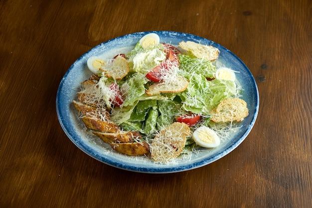 Классическое американское блюдо - салат цезарь с курицей, гренками, пармезаном и помидорами в синей тарелке на деревянной поверхности.