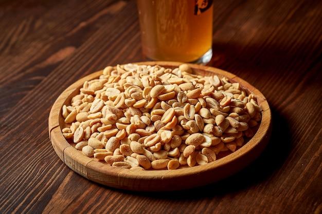 Классическая закуска к пиву - соленый жареный арахис на деревянной тарелке. продовольственный паб