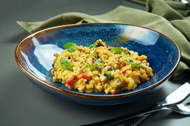 Классическое блюдо итальянской кухни - ризотто с морепродуктами, овощами и специями в синей миске на деревянном столе. крупным планом, селективный фокус