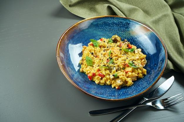 Классическое блюдо итальянской кухни - ризотто с морепродуктами, овощами и специями в синей миске на деревянном столе. закройте с копией пространства.