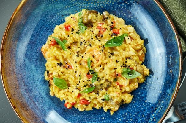 Классическое блюдо итальянской кухни - ризотто с морепродуктами, овощами и специями в синей миске на деревянном столе. вид сверху. закрыть