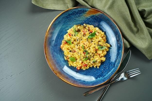 Классическое блюдо итальянской кухни - ризотто с морепродуктами, овощами и специями в синей миске на деревянном столе. вид сверху, плоская планировка с копией пространства