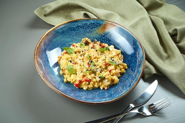Классическое блюдо итальянской кухни - ризотто с морепродуктами, овощами и специями в синей миске на деревянном столе