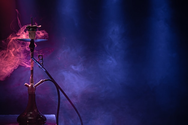 古典的な水ギセル。美しい色の光線と煙。水ギセル喫煙の概念。