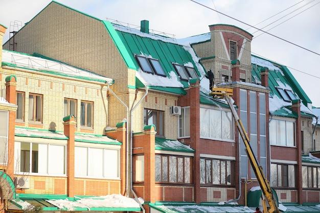 청소 서비스는 집 지붕의 눈을 청소합니다. 특수 장비를 사용하는 작업자들은 겨울에 눈을 청소합니다. 집 지붕의 얼음과 눈 청소.