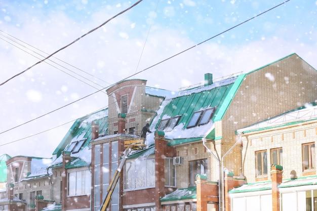Уборочная убирает снег с крыши дома. зимой рабочие на спецтехнике убирают снег. очистка от льда и снега крыш домов.