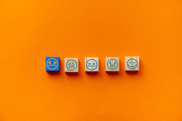 クライアントは、青い背景の木製の立方体にある悲しそうな顔のエンブレムと、カスタマーサービスの評価と満足度調査の概念を選択しました。